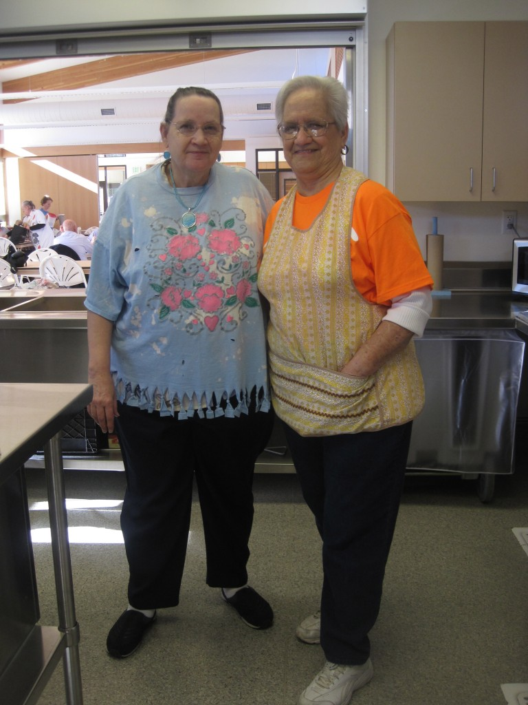Anne James stands with Nina Pew, 82, at right. Pew has been volunteering for the meals program for six years. Photo by Vanessa Salvia
