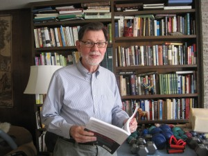 Bill Kievith is an avid reader of books about health and history. Here he is in front of just one of many bookshelves in his home. On the table in front of him is his collection of hand weights that he uses when he works out. Photo by Vanessa Salvia