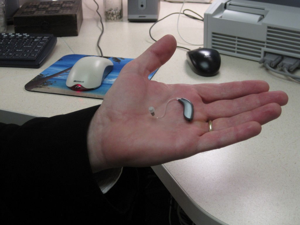 Dr. Brad Smith of Hearing Associates holds a small behind-the-ear hearing device. Photo by Vanessa Salvia