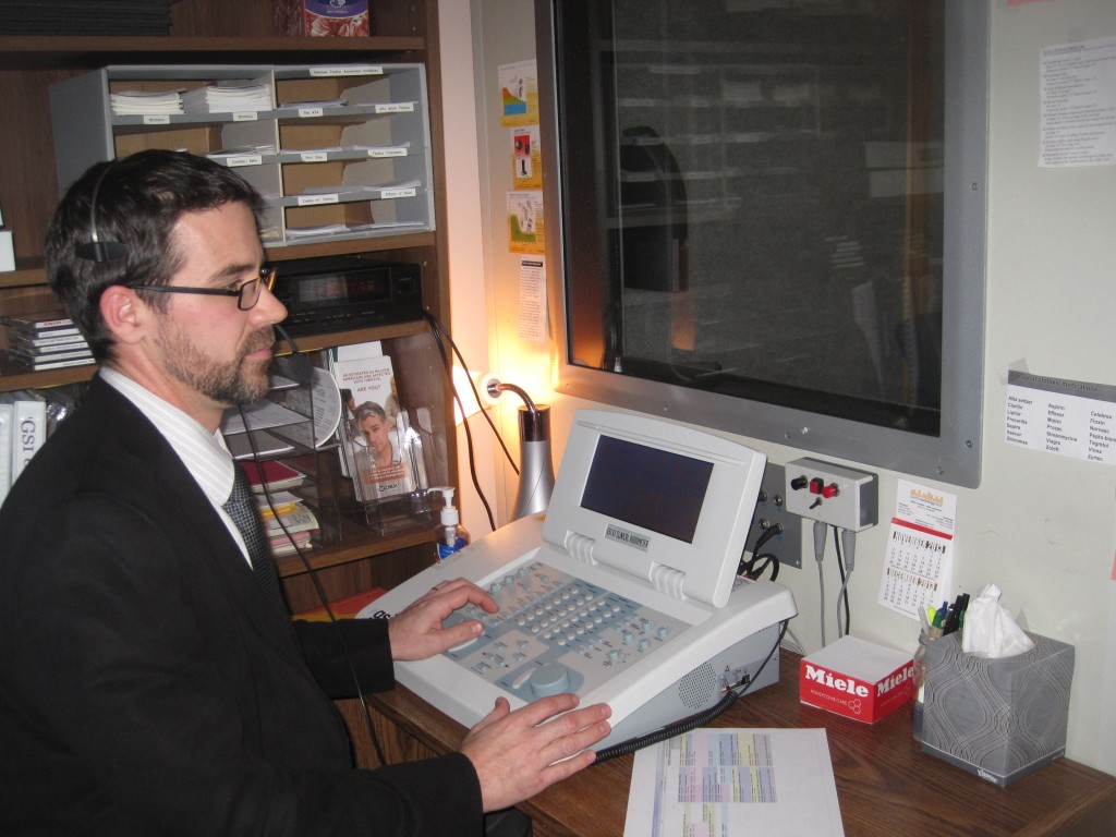 Dr. Brad Smith of Hearing Associates sits at the console where he conducts hearing tests. Photo by Vanessa Salvia