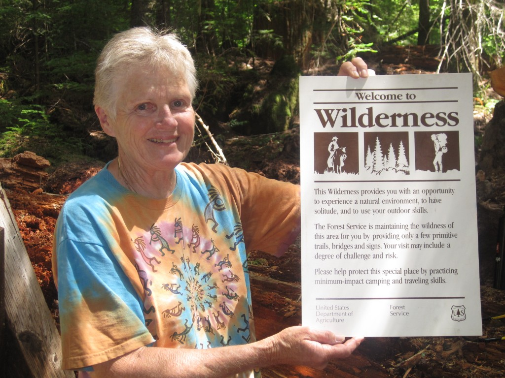 Volunteer leader Judy Mitchell holds the signage the crew will place on the assembled trailhead sign. Photo by Vanessa Salvia