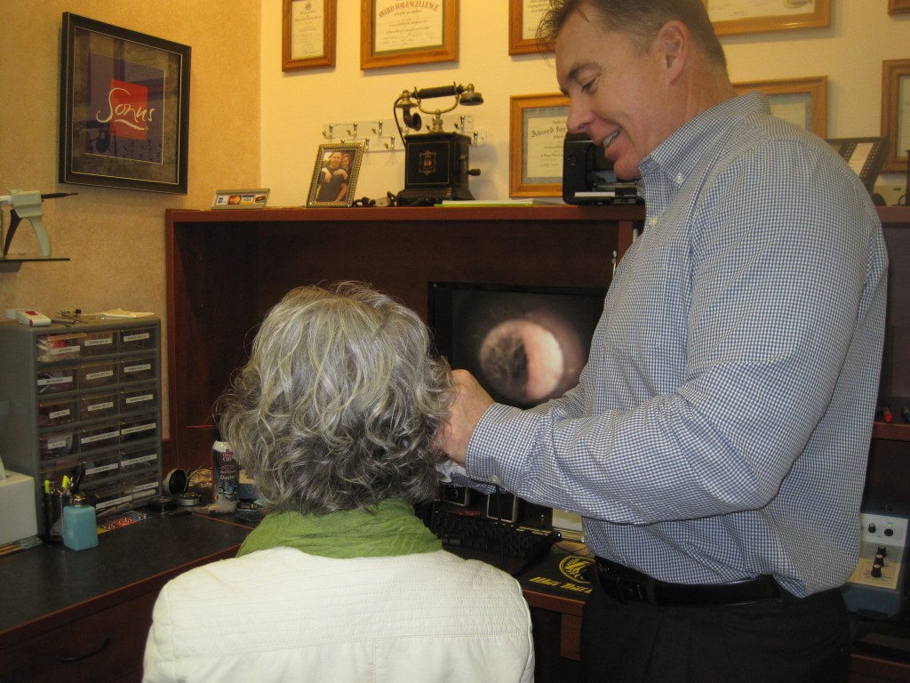 Grant Gording uses his otoscope to look into the ear of his secretary, Carla Baer. The otoscope projects the image of the ear on the computer screen behind them. Photo by Vanessa Salvia