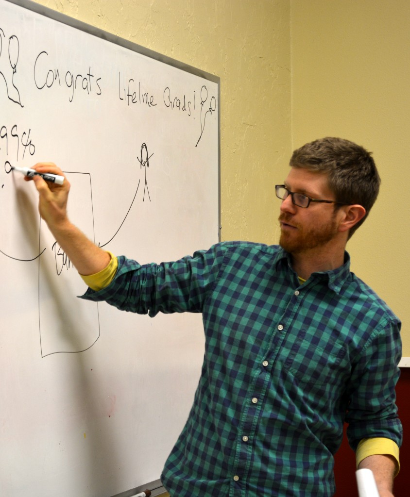 NEDCO instructor Ross Kanaga offers instruction on the board during one of his money management classes. Photo courtesy of NEDCO