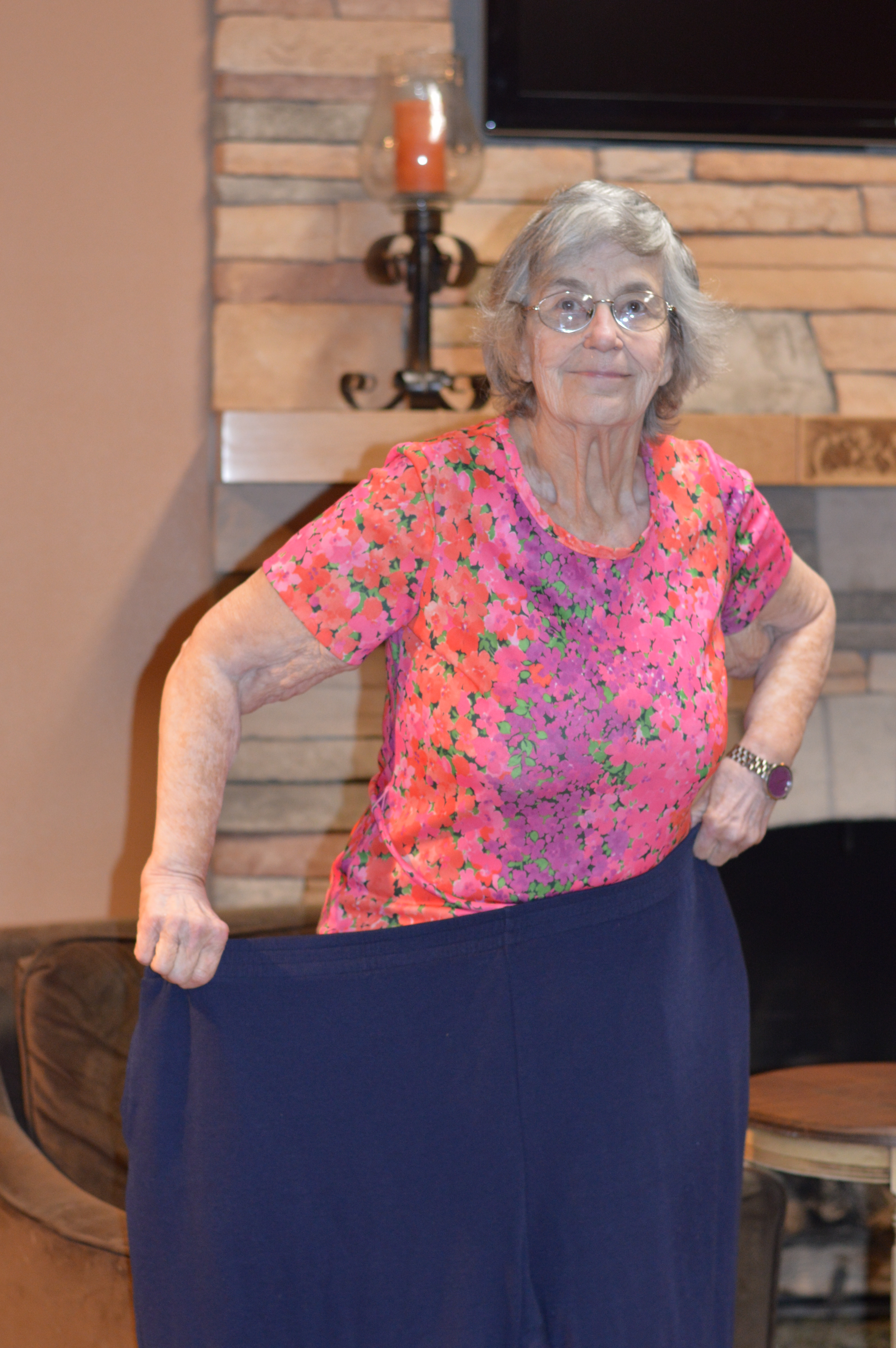 Mary Phillips, who was honored by Take Off Pounds Sensibly (TOPS) for reaching her goal weight loss of 164 pounds, holds up pants showing her at her largest. Photo by Vanessa Salvia.